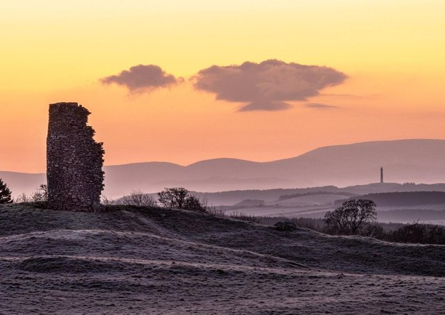A ruined windmill and Peniel Heugh monument against a backdrop of the Cheviot Hills are captured on a frosty morning prior to sunrise
