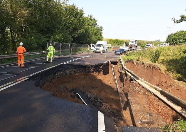 Fencing is put up where a massive section of the A68 between Pathhead and Fala Dam collapsed.