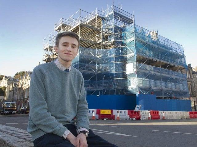 Scott Hamilton outside the scaffold-surrounded empty building in the square in Jedburgh. (BILL McBURNIE)