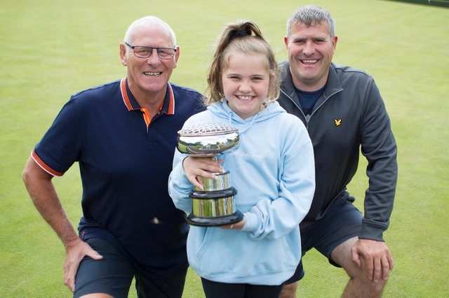 Ava Lindores lifts the cup won at Jedburgh Bowling Club by her father, Euan, and grandfather, Robbie, won in the pairs competition (picture by Bill McBurnie)