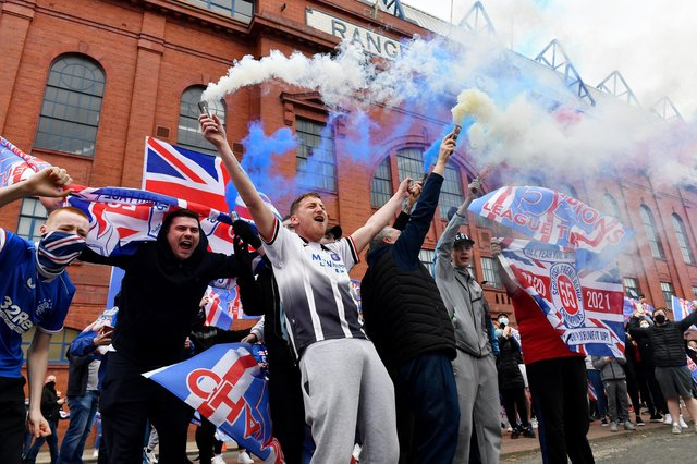 Rangers fans set off smoke bombs as they gather outside Glasgow's Ibrox Stadium to celebrate their team winning the Scottish Premiership title on March 7 (Photo by Mark Runnacles/Getty Images)