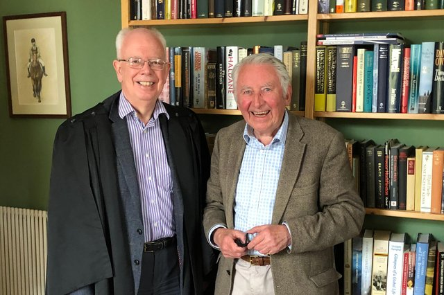 The new Moderator of the Church of Scotland, Lord Wallace, is presented a robe for the ceremony by Lord Steel of Aikwood.