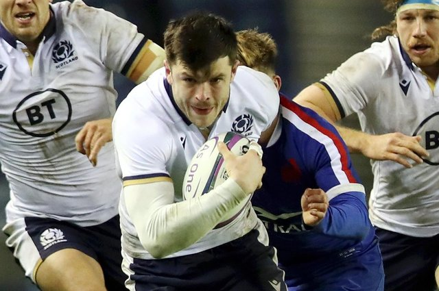 Blair Kinghorn makes a break for Scotland against France.